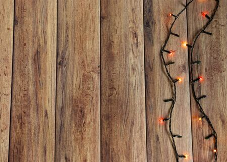 Colorful christmas garland lights on brown wooden background. Christmas Light with Copyspace for New Year Frame or Christmas Layout. New Year.