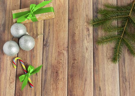 Christmas baubles, fir branches, gift, balls for the Christmas tree, candy canes, paper for text on a brown wooden table. Christmas wooden background. New Year, Christmas, winter holiday, copy space