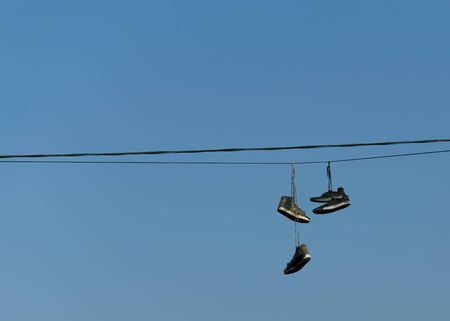 Old ripped sneakers hang on electric wires against the blue sky in the city. Hooliganism. Banco de Imagens