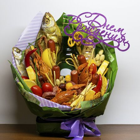 An edible gift in the form of a bouquet consisting of beer, sausages, cheese, beer snacks. Bouquet of beer snacks for mens birthday
