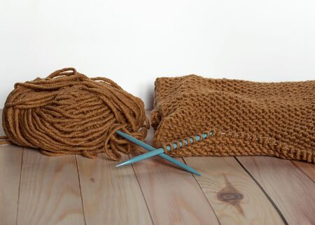Handwork and craft. Knitting with brown yarn. A ball of thread. Needlework