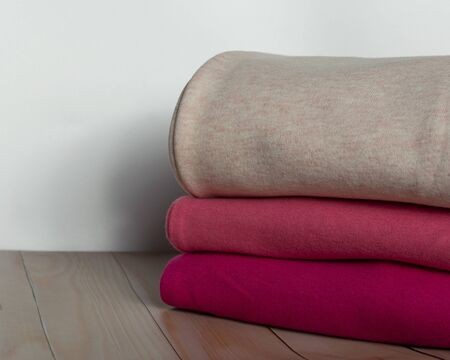 A pile of warm clothes on a wooden table. Clothes are stacked. Warm cozy winter autumn knitwear.