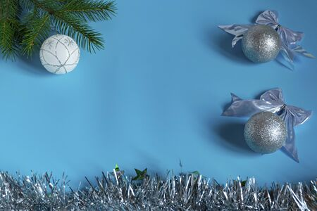 Silver shiny Christmas decorations, spruce branch, balls for the Christmas tree, bows, tinsel on a blue background, top view.