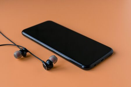 Black wireless bluetooth headphones for the phone on an orange background. Headset for the phone.