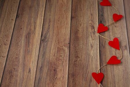 Background for Valentine's Day. Garland of hearts on a wooden background. Valentine .