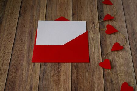 Background for Valentine's Day. Garland of hearts, red envelope on a wooden background. Valentine .