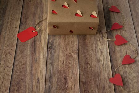 Background for Valentines Day. Garland of hearts, gift from craft paper on a wooden background. Valentine