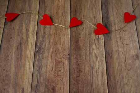 Background for Valentines Day. Garland of hearts on a wooden background. Valentine