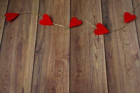 Hintergrund zum Valentinstag. Girlande von Herzen auf einem hölzernen Hintergrund. Valentin