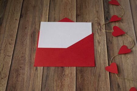 Background for Valentines Day. Garland of hearts, red envelope on a wooden background. Valentine