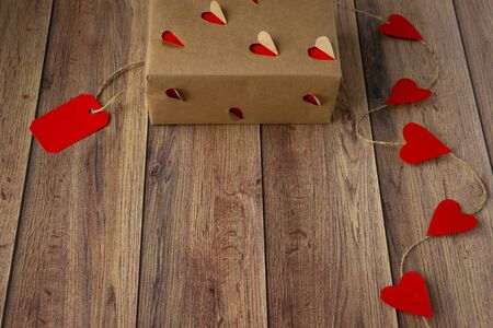 Background for Valentine's Day. Garland of hearts, gift from craft paper on a wooden background. Valentine .