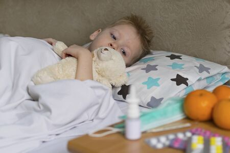 A sick sad child with a temperature and a headache lies in bed next to medication. Flu colds disease virus bacterium