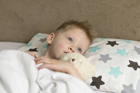 Sick sad child in temperature lies in bed with a toy bear. Flu colds disease virus bacterium