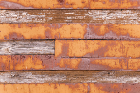 The wooden wall is covered with iron boards. Rusty boards. Stock Photo