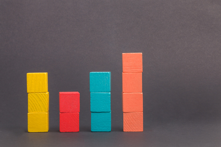 Toy wooden blocks as financial graph. Graph with four 4 steps. Infographic diagram, chart over grey or black or dark background. Multi-colored wooden blocks. Фото со стока