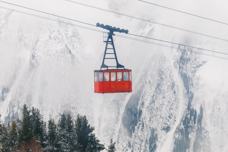 Red Ski lift in the background of the winter mountains. The red trailer of the old cable car moves to the mountain top of the ski resort. Retro gondola. 版權商用圖片