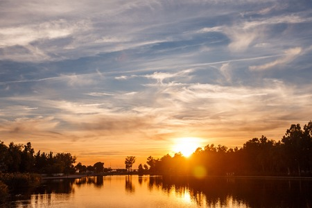 Sunset on the city pond. Lake in a small resort town. Beautiful evening clouds. Amazing card view. Banco de Imagens