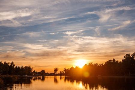 Zachód słońca nad stawem miejskim. Jezioro w małej miejscowości wypoczynkowej. Piękne wieczorne chmury. Niesamowity widok karty. Zdjęcie Seryjne