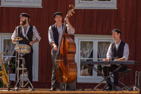 Stockholm, Sweden - 7 June 2019: Street musicians play on stage in front of the audience and passers-by. Funny three artists. Drum, saxophone, double bass, synthesizer. Three men. Editorial