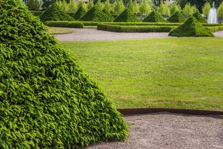 Uppsala, Sweden - 16 June 2019: Beautiful green park with green pyramids of trees and a fountain, in front of the building Linneanum orangery. One of the oldest botanical gardens in the world.
