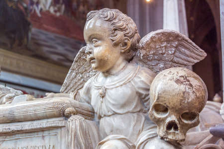 Uppsala, Sweden - 16 June 2019: Tomb of King Gustav Vasa and three of his wives in Uppsala Cathedral (Uppsala domkyrka). A little angel with wings and a skull in his hand. Monument to birth and death.