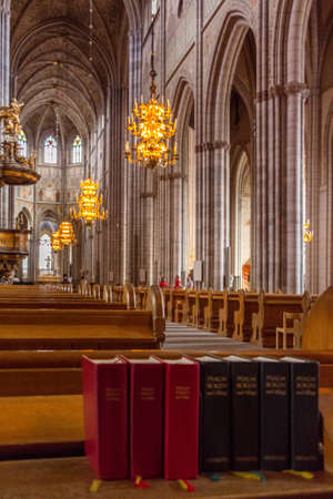 Uppsala, Sweden - 16 June 2019: Lots of red Bibles for the congregation of the Catholic Church. Hymnals and prayer books. Details of interior of Uppsala Cathedral. Books and Church on background.
