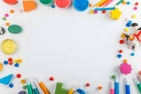 Top view of white tabletop with various drawing tools, finger paints, toy cow, white paper sheet. Mock up. Children's drawing table.