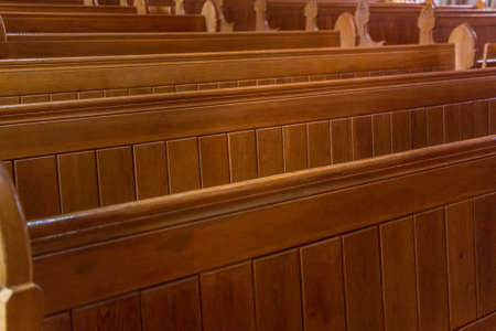 Empty old and wooden church pews without people.