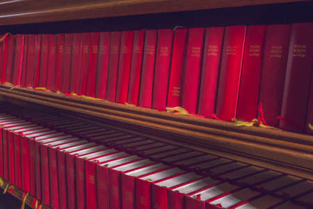 Uppsala, Sweden - 16 June 2019: Lots of red Bibles for the congregation of the Catholic Church. Hymnals and prayer books. Details of interior of Uppsala Cathedral.