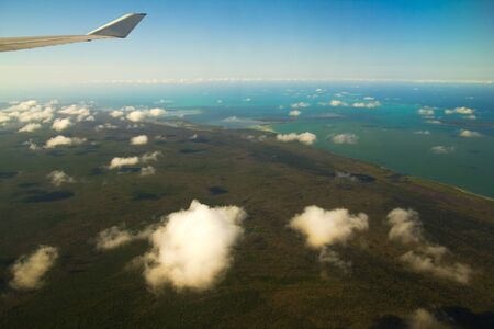 Blue sky with white clouds from the plane view.Cumulus clouds. Wing of the airplane can be seen. The Caribbean Sea.