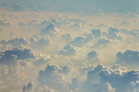 Blue sky with white clouds from the plane view.Cumulus clouds with interesting shadows.Beautiful amazing unusual multi-tiered clouds. Screensaver. Wallpaper. Background.