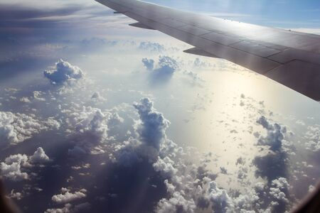 Blue sky with white clouds from the plane view.Cumulus clouds. Wing of the airplane can be seen.