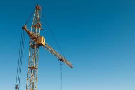 Top of a yellow construction hoisting crane against a blue sky background.