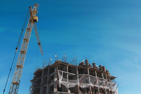 Construction site with crane and building with blue sky background. Foto de archivo