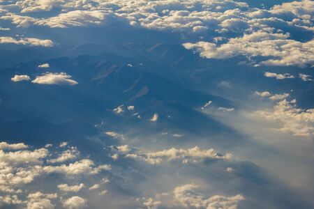 Blue sky with white clouds from the plane view.Cumulus clouds. Tops of mountains.