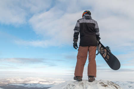 The snowboarder stands on the edge and holds the snowboard. The skier climbed the mountain. Freeride in the mountains. A young man extreme stands with a snowboard on top of a rock.