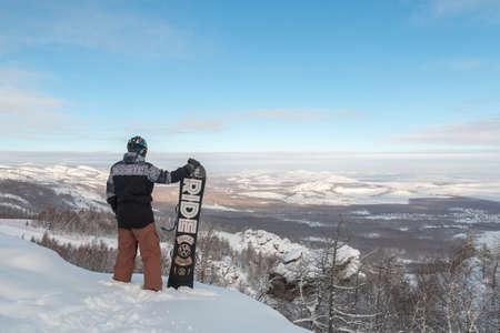 Man stay with snowboard equipment in hands on big rock. Snowboarder watch beautiful mountain view of Bannoe Ski, Bashkortostan, Russia. Reklamní fotografie
