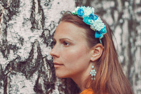 Smiling young woman wearing a decorative floral headband is looking at camera. Close-up portrait of a natural girl without makeup over a birch bark background. Spring is coming. Reklamní fotografie