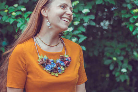 Laughing lovely young woman wearing a decorative floral necklace is looking away. Close-up portrait of a natural girl without makeup with tilted the head over a green background. Spring is coming.