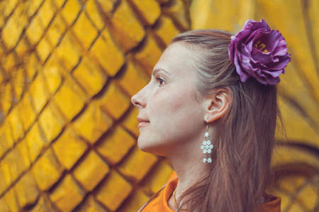 Lovely young woman wearing a decorative floral headpin is looking aside. Close-up portrait of a natural girl without makeup over a yellow geometric background.