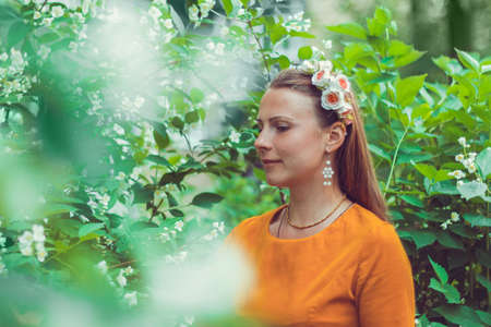 Smiling pretty young woman wearing a decorative floral headband is looking down away. Close-up portrait of a natural girl without makeup is enjoying the smell in blooming garden. Spring is coming. Reklamní fotografie