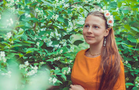 Smiling pretty young woman with long light brown hair wearing a decorative floral headband is looking down away. Portrait of a natural girl without makeup is enjoying the smell in blooming garden. Reklamní fotografie