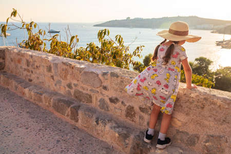 A little girl with a big hat looks at the sea and the city. A girl in the castle of Bodrum, Turkey. The baby is resting and going to the sights. Reklamní fotografie