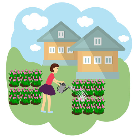 The girl is watering the flowers in a graze.
