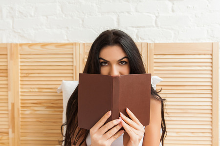 absorbed: Beautiful girl hiding her face behind the book
