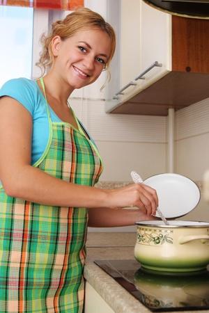 Woman prepares soup on kitchen 2 photo