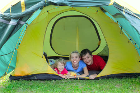 Happy family in tent on the nature photo
