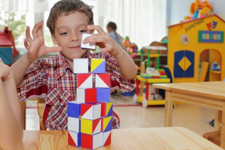 Happy boy in a kindergarten plays with cubes Stock Photo - 9290004