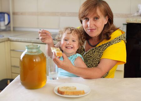 Happiness grandmother with the granddaughter eating honey with bread photo