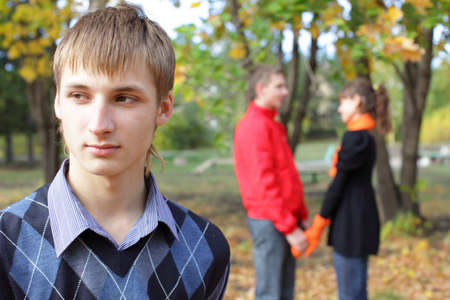 Sad young man against happiness couple photo